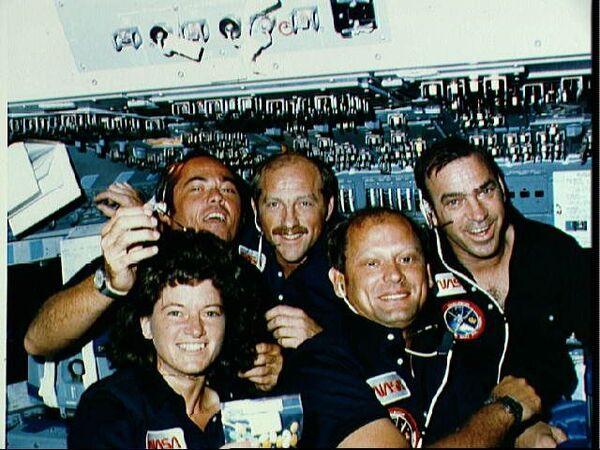 سالي رايد مع طاقم مهمة STS-7. من الخلف، من اليسار إلى اليمين: القائد روبرت إل. كريبن، طيار المكوك فريدريك هاوك، وأخصائي المهمة جون إم. فابيان. في المقدمة: أخصائية المهمة سالي رايد وأخصائي المهمة نورمان ثاجارد. حقوق الصورة: ناسا