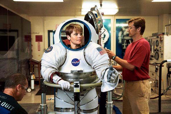"""نرى رائدة الفضاء ماكلين وهي تحاول تجربة نموذج تجريبي من بدلة رواد الفضاء. تقول ماكيلين: """"ارتداء بدلة الفضاء هو أمر شاق للغاية، إنه يشبه الدخول إلى طائرة صغيرة الحجم""""."""