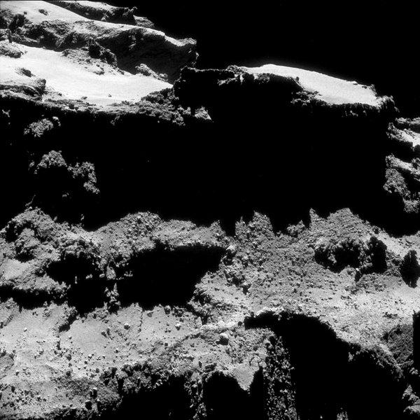 صورة ذات إطار واحد تم التقاطها بواسطة NAVCAM للمذنب 67P/C-G في 27 تشرين الأول/أكتوبر عام 2014 من على مسافة تبعد 9.8 كم من مركز المذنب. تمت معالجة الصورة بشكل طفيف بهدف إظهار التفاصيل على سطح المذنب. المصدر: ESA/Rosetta/NAVCAM – CC BY-SA IGO 3.0