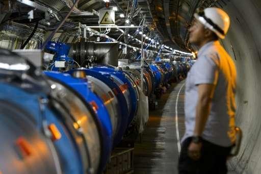 عالم ينظر إلى أحد الأقسام في مصادم الهادرونات الكبير أثناء الصيانة التي جرت في ميرن بالقرب من جنيف في 19 يوليو/تموز 2013.