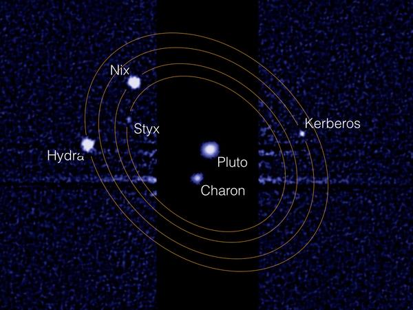 """تُظهر هذه الصورة، المُركّبة من تلسكوب هابل الفضائي، بلوتو وأكبر أقماره """"شارون"""" في المنتصف. تدور أقمار بلوتو الأربعة الأصغر حول هذا """"الكوكب الثنائي"""" ويمكن رؤيتها في يمين ويسار الصورة.. مصدر الصورة ناسا / م. شوالتر (NASA/M. Showalter)"""