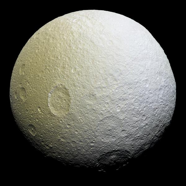 تُظهِر هذه الصورة الفسيفسائية مُحسَّنة اللون لقمر تيثيس مجموعةً من الملامح على نصف القمر التابع؛ حيث أن تيثيس مرتبط مع زحل بقوى مدية، ومن ثمّ فإن النصف التابع هو جانب القمر الذي يواجه دائماً عكس اتجاه حركته أثناء دورانه حول الكوكب. المصدر: ناسا/ مختبر الدفع النفاث (JPL)/ معهد علوم الفضاء (Space Science Institute).