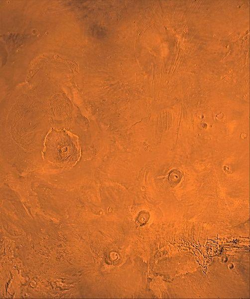 منطقة ثارسيس البركانية الخاصة بالمريخ كما يمكن مشاهدتها بواسطة بعثة ناسا Viking. في اليسار يوجد بركان أوليمبس مونز Olympus Mon الضخم. سلسلة البراكين في أسفل اليمين تتألف من آرسيا Arsia وبافونيس Pavonis وأسكريوس مونز Ascraeus Mons من الأسفل إلى الأعلى. حقوق الصورة: NASA/JPL/USGS