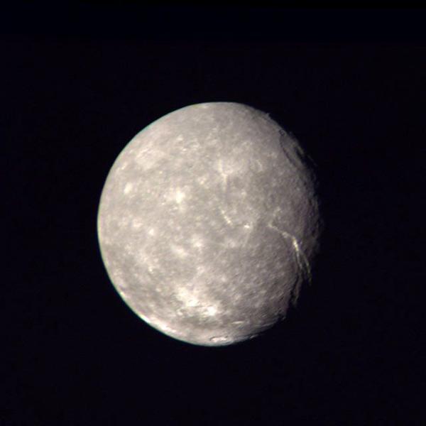 """تبين هذه الصورة، التي التقطتها المركبة """"فوياجر 2"""" قمر """"تيتانيا"""" التابع لـ """"أورانوس""""، وتظهر شدة الفوهات الموجودة على سطحه حقوق الصورة:.  NASA"""