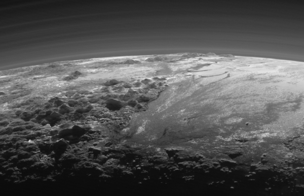 نظرة مقربة: تظهر في هذه الصورة الجبال الجليدية الكبيرة لبلوتو والسهول الجليدية المتجمدة بالإضافة إلى طبقات من الضباب. وقد تم التقاط هذه الصورة بعد 15 دقيقة فقط من وصول نيو هورايزنز إلى أقرب نقطة لها من بلوتو بتاريخ 14 يوليو/تموز 2015. وبينما كانت المركبة تنظر إلى الوراء باتجاه الشمس، تمكنت من التقاط هذه المشاهد المقربة لغروبها والتي تظهر فيها الجبال الجليدية الوعرة بالإضافة إلى السهول الجليدية المسطحة التي تمتد باتجاه أفق بلوتو.  يطلق على هذه المساحة المسطحة اسم غير رسمي هو السهل الجليدي سبوتنيك بلاينم Sputnik Planum(إلى جهة اليمين). وتحيط بهذا السهل من جهة الغرب سلسلة من الجبال الوعرة التي يصل ارتفاعها إلى 11 ألف قدم (أي 3500 كم)، بما فيها جبال نورغاي Norgay Montes (وهو اسم غير رسمي) التي توجد في المقدمة، وجبال هيلاريHillary Montes التي توجد في الأفق. ويتم قطع التضاريس الوعرة التي توجد إلى اليمين أي شرقي سبوتنيك، بواسطة الأنهار الجليدية التي تبدو واضحة للعيان. ويُسلَّط ضوء الخلفية على أكثر من اثني عشرة طبقة من الضباب الموجود في الغلاف الجوي الممتد والرقيق لبلوتو. تم التقاط هذه الصورة من نقطة تبعد عن بلوتو مسافة تقدر بـ 11 ألف ميل (أي 18 ألف كم)، ويقدر نطاق هذه الصورة بـ 230 ميلاً (أي 380 كم). المصدر: NASA/JHUAPL/SwRI