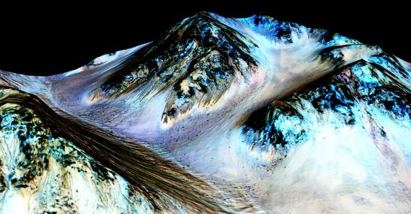 """يُشير العلماء إلى أن هذه الخطوط الداكنة الضيقة البالغ طولها حوالي 100 متر والمعروفة باسم """"خطوط المنحدرات المتكررة"""" (recurring slope lineae) التي تجري نحو الأسفل على هذه المنحدرات المريخية الظاهرة في الصورة أعلاه قد تشكّلت بفعل الماء الجاري على سطح الكوكب حالياً، أي أنها حديثة التشكّل. ومؤخراً، رصد العلماء المختصون بعلوم الكواكب وجود أملاح مائية على هذه المنحدرات الموجودة في فوهة هيل، ما يُعزز الفرضية الأصلية السابقة التي تقول بأن هذه الخطوط تشكّلت بالفعل بسبب الماء السائل. ويعتقد العلماء أن اللون الأزرق الظاهر في قمة المنحدر عند الخطوط الداكنة ليس له علاقة بتشكل هذه الخطوط، بل هو ناتج عن وجود معدن البيروكسين. أُنتجت الصورة عبر وضع صورة مُصححة متعامدة بألوان زائفة (ما تحت الحمراء-الأزرق/الأخضر (IRB) (إي أس بي_030570_1440) على نموذج التضاريس الرقمي (DTM) الخاص بالموقع نفسه والذي أنتجته تجربة التصوير العلمي عالي الدقة High Resolution Imaging Science Experiment، أو اختصاراً (HiRISE) في جامعة أريزونا. يبلغ مستوى التضخيم العمودي Vertical Exaggeration حوالي 1.5 درجة.   حقوق الصورة: NASA/JPL/University of Arizona"""