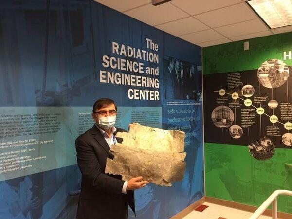 كنان أونلو يقف مع شريحة الألمنيوم التي يُعتقد أنها جزء من طائرة إيرهارت. (حقوق الصورة: Kenan Ünlü/Penn State)