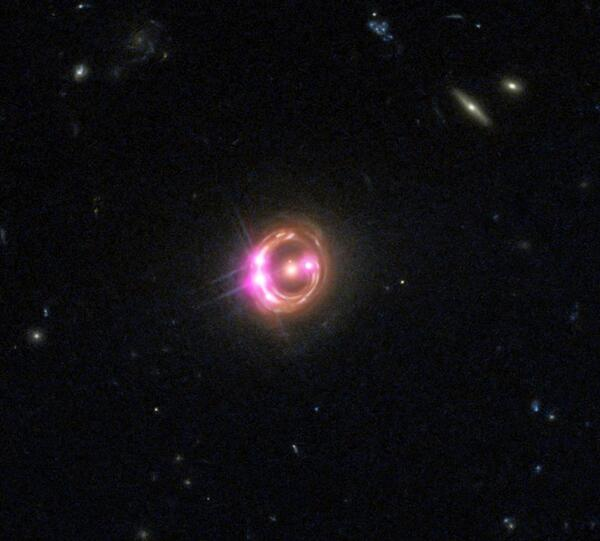 كوازار (quasar) بعيد للغاية يظهر الكثير من الأدلة على وجود ثقب أسود هائل في مركزه. كيف أصبح هذا الثقب الأسود بهذه الضخامة بهذه السرعة هو موضوع جدل علمي، لكن اندماج الثقوب السوداء الأصغر التي تشكلت من الأجيال الأولى من النجوم قد توفر الأصول اللازمة. تتفوق العديد من الكوازارات في سطوعها حتى على أكثر المجرات سطوعًا. حقوق الصورة: X-ray: NASA/CXC/Univ of Michigan/R.C.Reis et al; Optical: NASA/STScI