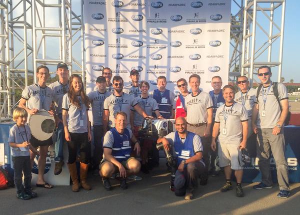 """العديد من أعضاء فريق روبوسيميان والقليل من الضيوف مجتمعين مع الأجهزة المنافسة في """"لقاء الروبوتات"""" خلال نهائيات تحدي الروبوتات في بومونا، كاليفورنيا، في 6 يونيو 2015. حقوق الصورة: JPL_معهد كاليفورنيا للتكنولوجيا (Caltech)"""