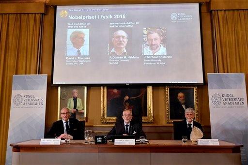 """تظهر الصورة أعضاء الأكاديمية الملكية للعلوم. من اليسار، البروفيسور نيلس مارتينسون، البروفيسور غوران ك. هانسون والبروفيسور توماس هانس هانسون وهم يعلنون عن أسماء الفائزين بجائزة نوبل في الفيزياء، في الأكاديمية السويدية الملكية للعلوم في ستوكهولم، السويد، الثلاثاء 4 تشرين الأول/أكتوبر 2016، حيث فاز بجائزة نوبل للفيزياء كل من ديفيد ثاوليس ودانكن هالدين ومايكل كوستيرليتز حيث تشيد لجنة التحكيم الفائزين الفيزياء لاكتشافاتهم في اانتقالات الطور الطوبولوجية والأطوار الطوبولوجية للمادة"""".  المصدر (Anders Wiklund /TT via AP)"""