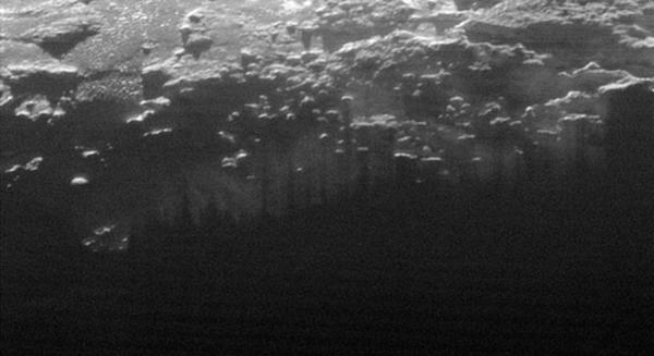 الضباب المتشكل بالقرب من سطح بلوتو: نرى في هذا الجزء الصغير من صورة أكبر لبلوتو التقطتها مركبة نيوهورايزنز بعد 15 دقيقة فقط من وصولها إلى أقرب نقطة لها من بلوتو بتاريخ 14 يوليو/تموز، ضوء الشمس وهو ينير طبقات الضباب المتشكل بالقرب من السطح. ويتخلل الضباب خطوط متوازية من الظلال في العديد من التلال المحلية والجبال الصغيرة. وقد تم التقاط هذه الصورة من نقطة تبعد عن بلوتو مسافة تقدر بـ 11 ألف ميل (أي 18 ألف كم)، ويقدر نطاق هذه الصورة بـ 115 ميلاً (أي 185 كم). المصدر: NASA/JHUAPL/SwRI