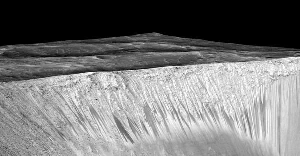 تُظهر هذه الصورة خطوطاً مُظلمة وضيقة تُسمى خطوط المنحدرات المتكررة وهي تمتد على طول جدران فوهة غارني على كوكب المريخ. يبلغ طول الخطوط الداكنة هذه بضع مئات من الأمتار، ويفترض العلماء أنها تشكّلت بسبب تدفق الماء المالح السائل على السطح. أُنتجت الصورة عبر وضع صورة مُصححة مُتعامدة (orthorectified) (RED) (إي أس بي_031059_1685) على نموذج التضاريس الرقمي (DTM) للموقع نفسه الذي أنتجته تجربة التصوير العلمي عالي الدقة (جامعة أريزونا). يبلغ مستوى التضخيم العمودي حوالي 1.5 درجة. حقوق الصورة: Credits: NASA/JPL/University of Arizona