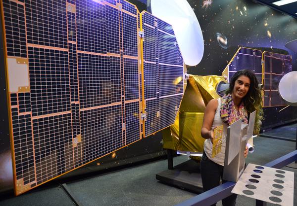 تحمل فرح أليباي (Farah Alibay)،مهندسة نظام للتكنولوجيا التوضيحية ، نموذجاً كاملَ الحجم للكيوب سات ماركو (MarCo Cubesat) و الذي يتقزم حجمه أمام نموذج بنصف حجم مستكشف المريخ المداري (Mars Reconnaissance Orbiter) التابع لناسا.