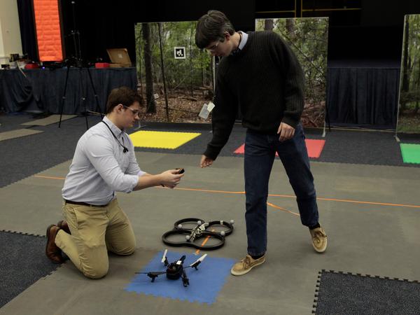 الزميلين جيلبرت مونتيجو Gilbert Montague على اليسار، وتشارلز كروس Charles Cross من فريق الحاضنة ذاتية التحكم يعدان الكوادريكوبتر UAV لبرهنة داخل مركز لانغلي للتحكم الذاتي والروبوتات.