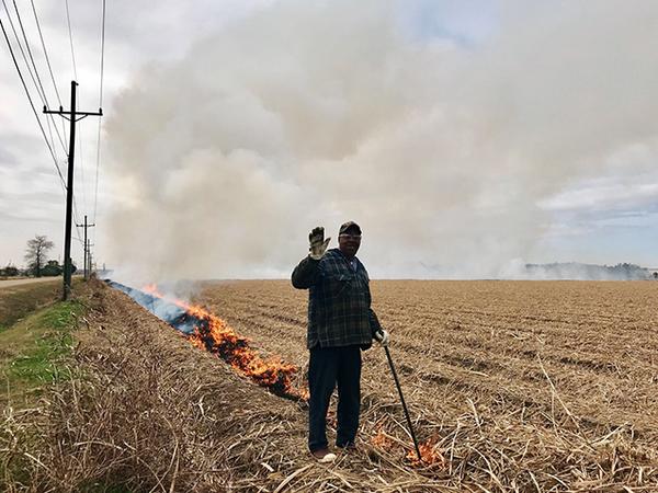يعمد المزارعون غالبًا إلى إضرام النار في الحقول الزراعية لتنقيتها وتطهيرها، لكن هذه الممارسة تزيد من تلوث الهواء. توضح هذه الصورة رجلًا يشعل حريقًا في حقلٍ بلويزيانا. تصوير: Chloe Gao