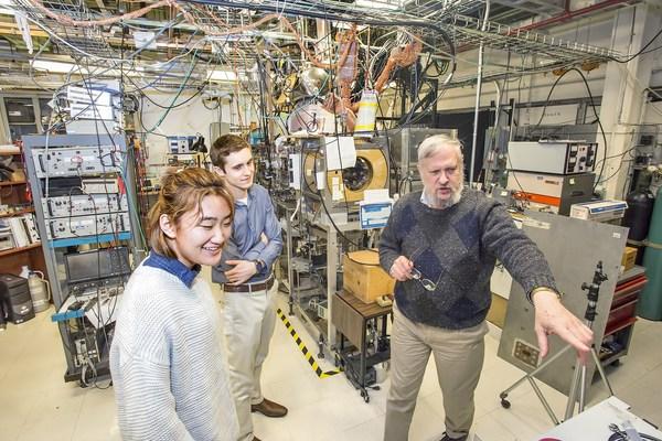 يقوم طالبان متدربان بجولة في مختبر جامعة برينستون لفيزياء البلازما مع الدكتور صموئيل كوهين (مرجع الصورة: شركة برينستون ساتلايت سيستمز).