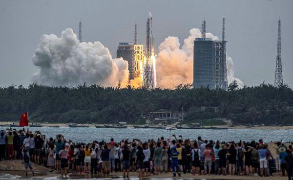 الناس وهم يشاهدون إطلاق صاروخ لونج مارش 5 بي، الذي حمل الوحدة الأساسية لمحطة الفضاء الصينية، تيانهي، من موقع إطلاق محطة وينتشانغ في 29 أبريل 2021. حقوق الصورة: STR/AFP/Getty