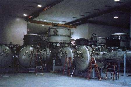 بحلول فبراير/شباط لعام 1998، رُكبت معدات التفريغ على شكل حرف L، ويأوي الخزان المركزي العمودي على مقسم الأشعة. يمتد الجانب الأيمن لأنابيب الأشعة نحو الصحراء، حقوق الصورة: LIGO. Credit: LIGO.