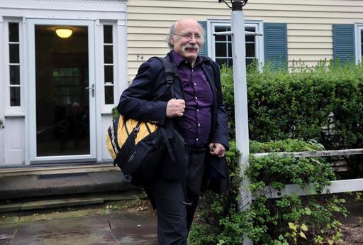 تظهر الصورة أستاذ الفيزياء بجامعة برينستون دنكان هالدين يغادر منزله بعد أن أعلن عن فوزه بجائزة نوبل في الفيزياء لعام 2016، ويقاسمه الجائزة كل من ديفيد ثاوليس ومايكل كوستيرليتز.  المصدر : (AP Photo/Mel Evans)
