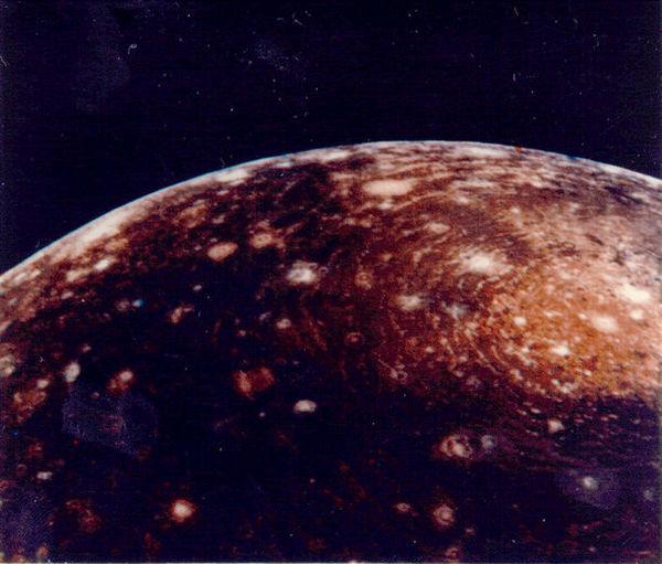 """التقطت مركبة فوياجر 1 هذه الصورة لكاليستو من مسافة 350,000 كم. ويُعتقد أنّ الدائرة الكبيرة """"عين الثور"""" الموجودة على القمة نتيجة قوة اصطدام الحوض المتشكل خلال وقت سابق في تاريخ هذا القمر. يبلغ عرض المركز المضيء للحوض حوالي 600 كم والحلقة أو الدائرة الخارجية يبلغ عرضها 2600 كم. حقوق الصورة: NASA/NSSDC Photo Gallery"""