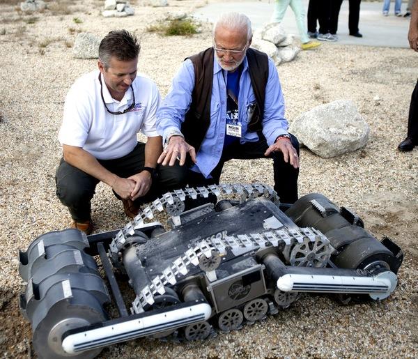 روب مولر Rob Mueller (إلى اليسار)، كبير علماء التكنولوجيا في في مكتب الأنظمة السطحية في مركز كنيدي للفضاء التابع لناسا، وهو يتحدث مع رائد الفضاء السابق في مهام )جيمني وأبولو باز الدرين (Buzz Aldrin) خلال استعراض.(RASSOR)