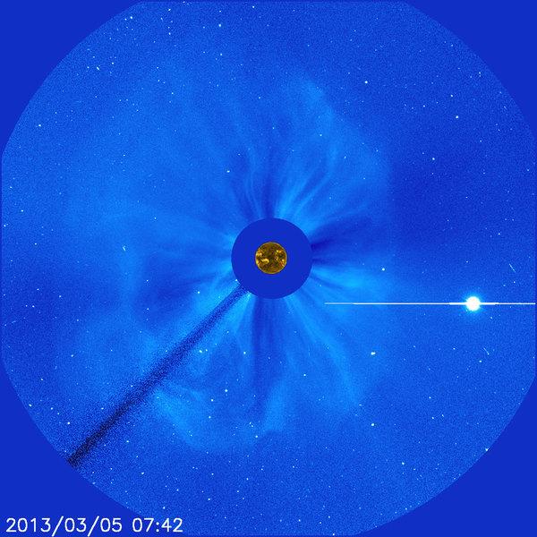 """التقطت هذه الصورة """"للانبعاث الكتلي الإكليلي"""" (coronal mass ejection) أو اختصاراً CME، بواسطة مرصد سوهو في 5 مارس/آذار 2013.  هذا الحدث هو هالة من الانبعاث الكتلي الإكليلي (halo CME)، سمي بذلك بسبب طريقة انتشار الغيمة المتوهجة من المواد الشمسية حول قرص الشمس في دائرةٍ خافتة.  قبل أن يكتشف سوهو التسونامي الشمسي الذي يحدث عادةً بالاقتران مع الانبعاثات الكتلية، لم يكن بمقدور العلماء أن يكتشفوا بأي شكلٍ من الأشكال ما إذا كانت هالة الانبعاثات الكتلية الإكليلية تتحرك مباشرةً باتجاه الأرض أو بعيداً عنها.  النقطة المضيئة في أسفل الصورة من اليمين هي كوكب الزهرة.  المصدر: وكالة الفضاء الأوروبية/ ناسا/ سوهو. ESA/NASA/SOHO."""