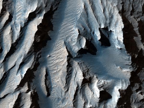يُقطع تايثونيم كازما (جزء من وادي مارينر بالمريخ) بخطوط قطرية من الرواسب التي يمكن أن تشير إلى دورات قديمة من التجمد والذوبان. مصدر الصورة: ناسا/مختبر الدفع النفاث/جامعة أريزونا.