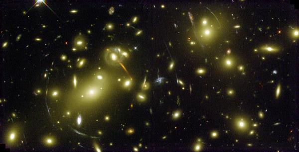 تُوضح الصورة جاذبية العنقود المجري Abell 2218 وقيام هذه الجاذبية بخلق عدسات عملاقة. صُورت الصورة باستخدام تلسكوب هابل الفضائي. حقوق الصورة: ناسا
