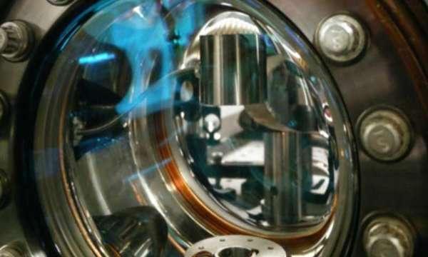يمكن مشاهدة أسطوانة التنغستين البرّاقة في الأعلى عبر نافذة في حجرة تخلخل الضغط في مقياس تداخل الذرات، وتُطلق ذرات السيزيوم نحو الأعلى عبر الفتحة الدائرية أسفل الأسطوانة. حقوق الصورة: Holger Müller lab, UC Berkeley