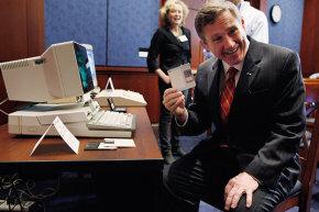 عضو مجلس الشيوخ الأميركي مارك كيرك Mark Kirk يسحب قرص مرن مقاس 3.5 بوصة من جهاز IBM PC Convergable. عُرِضت هذه الآلة الأثرية كجزء من الذكرى السنوية الخامسة والعشرين لقانون خصوصية الاتصالات الإلكترونية في عام 2011.حقوق الصورة: GETTY IMAGES