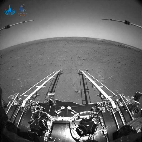 التُقطت صورة الأبيض والأسود بواسطة كاميرا تجنب العوائق الموضوعة في مقدمة المركبة الجوالة. نُشرت الصورة في 19 مايو 2021 بعد نحو 4 أيام من هبوط المركبة. في هذه الصورة ذات زاوية الرؤية الواسعة، يمكن رؤية منحدر نزول المركبة الجوالة، وكذلك جهازي الرادار تحت السطحي وأفق المريخ. حقوق الصورة: إدارة الفضاء الوطنية الصينية
