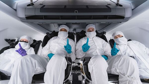 """رواد فضاء سبيس إكس-1 ، بمن فيهم رواد فضاء ناسا شانون ووكر وفيكتور جلوفر ومايكل هوبكنز ورائد فضاء جاكسا سويشي نوجوتشي، يقفون أمام كبسولة دراغون الخاصة بهم """"رزيليانس"""" في مقر سبيس إكس في هوثورن، كاليفورنيا (حقوق الصورة: SpaceX)"""