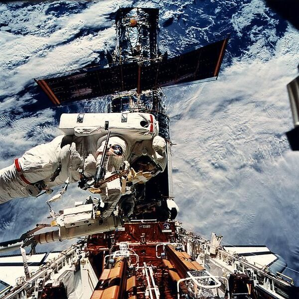 رائدة الفضاء التابعة لناسا كاثي ثورنتون تدخل عتاد إصلاح هابل خلال مهمة الخدمة الأولى في 1993. (حقوق الصورة: NASA)
