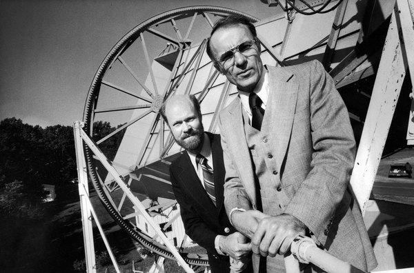 روبرت ويلسون (اليسار) وآرنو بينزياس خلفهم الهوائي الذي استخدماه لإيجاد إشعاع الخلفية الكونية الميكروي.