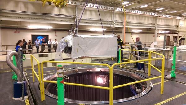 ينزل الفنيون جهاز الكشف ISS-CREAM داخل حجرة تحاكي البيئة الفضائية، خلال اختبار مستوى النظام، في مركز غودارد لرحلات الفضاء، في صيف 2015. مصدر الصورة: المختبر الفيزيائي للأشعة الكونية في جامعة ميريلاند.