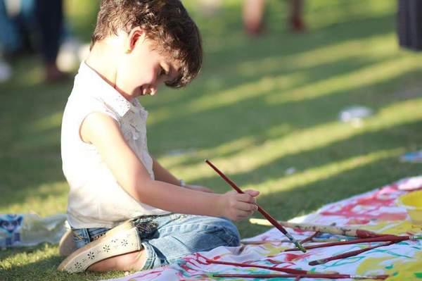 مشاركٌ صغير في نشاط الرسم الخاص بالأطفال وهو أحد فعاليات المهرجان