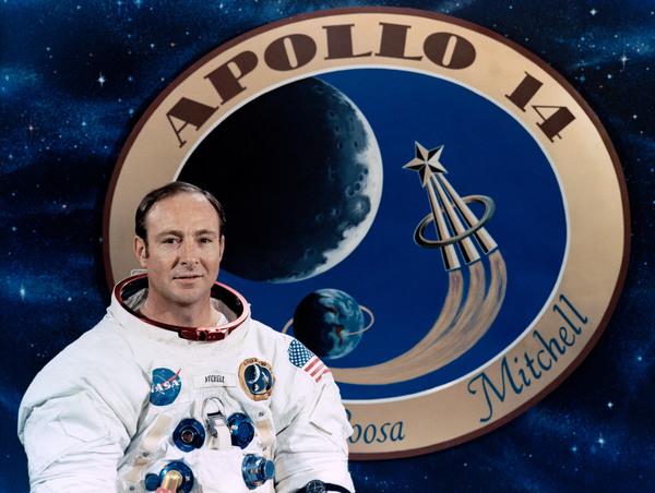 رائد الفضاء إدجار ميتشيل يقف أمام ملصق للرحلة أبوللو. حقوق الصورة: ناسا