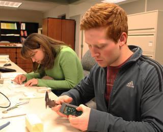 هانا لابوش وتريفور ساتلر، وهما يعملان على عناصر (مواد) تجربة ديزرت كريستيان والتي من المتوقّع انطلاقها في شهر مارس عام 2016، حيث أنّ هذه التجربة هي تكملةٌ لتجربة 3 ديسمبر Credits: NASA Photo / Jay Levine