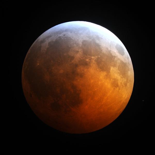 صورة التقطها جيمي ويستليك Jimmy Westlake للخسوف الكلي الذي حدث في العشرين من ديسمبر/ كانون الأول عام 2010، وهي تظهر الحافة الزرقاء لظل الأرض في مقابل الجزء الأحمر من القمر.  المصدر: جيمي ويستليك Jimmy Westlake