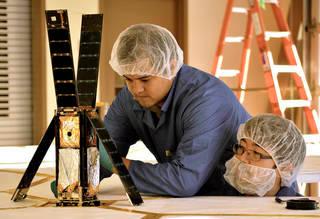 اثنان من أعضاء فريق لايتسيل، وهما أليكس دياز وريكي موناكاتا، وهما يحضّران المركبة الفضائية لاختبار فتح الأشرعة. المصدر: The Planetary Society