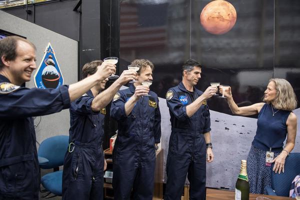 ليزا سبينس Lisa Spence، مديرة مشروع الطيران التناظري، تشرب عصير العنب مع طاقم هيرا 13 نخب النهاية الناجحة لمهمة الـ 45 يومًا الأولى. حقوق الصورة: NASA.