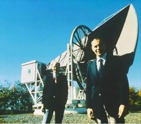 تظهر الصورة كلاً من ويلسون (في المقدمة)، مع بينزياس أمام الهوائي البوقي في مختبرات بيل. Credit: wikimedia