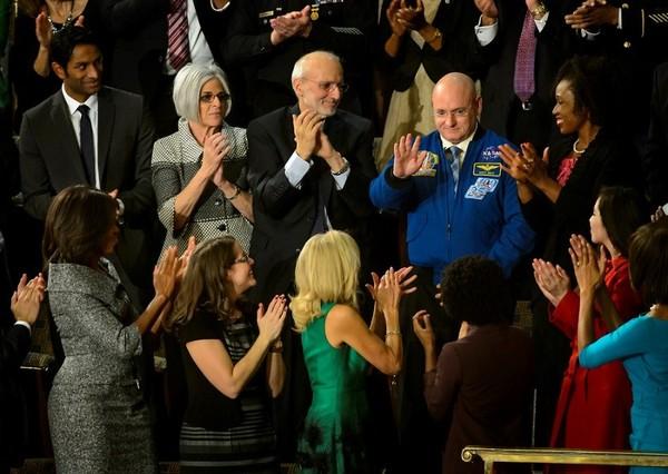 (سكوت كيلي يقف بينما تتم الإشارة إليه من قبل الرئيس باراك أوباما، بينما السيدة الأولى ميشيل أوباما (إلى الأسفل من الزاوية اليسرى) وآخرون من الحضور يقومون بالتصفيق)، الرئيس أوباما قام بذكر كيلي خلال خطاب الاتحاد السياسي في مبنى الكابيتول في العاصمة واشنطن في العشرين من كانون الثاني/يناير من العام 2015. مصدر الصورة: (NASA/Bill Ingalls)