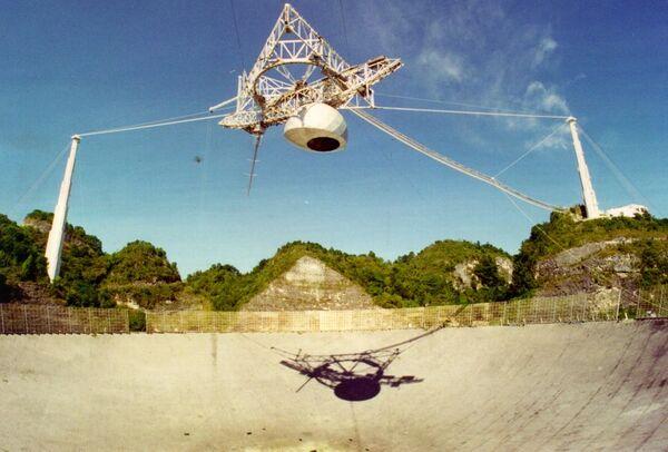 تُظهر هذه الصورة الأرشيفية للطبق الراديوي الضخم في مرصد أريسيبو المنصة العلمية الثقيلة المعلقة فوقه، واثنان من الأبراج الداعمة والكابلات الداعمة لها. حقوق الصورة: Courtesy of the NAIC - Arecibo Observatory, a facility of the NSF