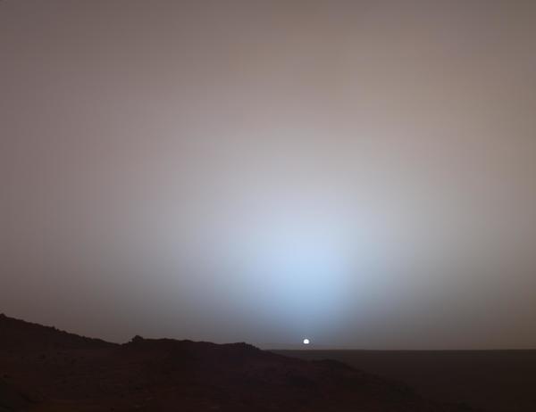 """لقطة واسعة لغروب الشمس في """"فوهة غوسيف"""" Gusev، تم التقاطها بواسطة المسبار """"روفر"""" التابع لناسا في عام 2005. نشاهد فيها هالةً زرقاء وسماءً ورديّة اللّون، وذلك بسبب طبيعة غبار المريخ الناعمة"""