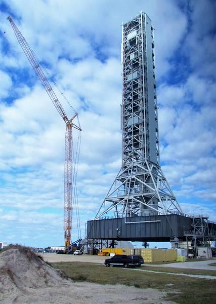 منصة إطلاق الصواريخ الفضائية مع البرج الحديدي الذي يدعم الهيكل الصاروخي قُبيل الإقلاع ويظهر في الصورة مدى ارتفاعه الموازي للرافعة العملاقة بجانبه