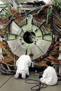 مهندسون يركبون مغناطيسا عملاقا داخل مصادم الهادرونات الكبير، وهو مسرع جسيمات ضخم.   حقوق الصورة : Fabrice, Coffrini/AFP/Getty Images .