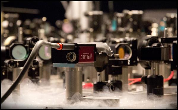 تُوضِحُ الصورةُ جانباً من التجاربِ القائمةِ على التقنيةِ الكموميةِ المعتمدةِ على نقلِ الضوءِ (الفوتونات) عبرَ ضوئياتٍ كُموميةٍ في المختبرِ التابعِ لمعهدِ نيلس بور في كوبنهاغن. حقوق الصورة: Ola Jakup Joensen