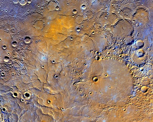 تظهر السهول البركانية الشمالية في عطارد بألوان معدّلة لإظهار الألوان المختلفة للصخور على سطح الكوكب. في الجزء السفلي الأيمن من الصورة يظهر حوض مندلسون Mendelssohn الذي يبلغ قطره 181 ميل (291 كيلومتر)، والذي سمي تيمناً بالموسيقار الألماني، ويبدو فيها أنه قد كان مليئاً في السابق بالحمم البركانية. أما في الجزء السفلي الأيسر فتظهر تلال متعرجة تشكلت عندما بردت الحمم البركانية. ويمكن التعرف أيضاً على الحفر التي دفنتها الحمم البركانية في هذه المنطقة. بالقرب من أعلى الصورة، تظهر منطقة برتقالية زاهية وهي موقع فوهة البركان. مصدر الصورة: NASA/JHUAPL/Carnegie Institution of Washington