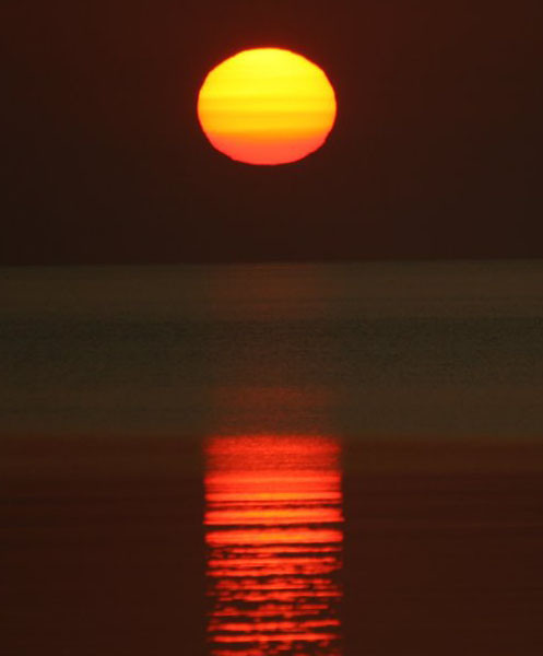 """شروق الشمس من بحيرة """"سوبيريور"""". يعمل انكسار جوي """"يكسر أشعة الشمس"""" على تسطيح قرص الشمس، مُظهرًا إيّاه بشكل بيضاوي.  المصدر: لاين أندرسون."""